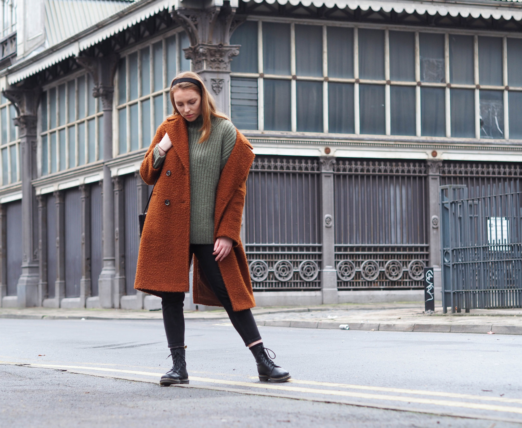 girl in Manchester wearing orange wool coat, khaki green and other stories knit and black dr marten boots