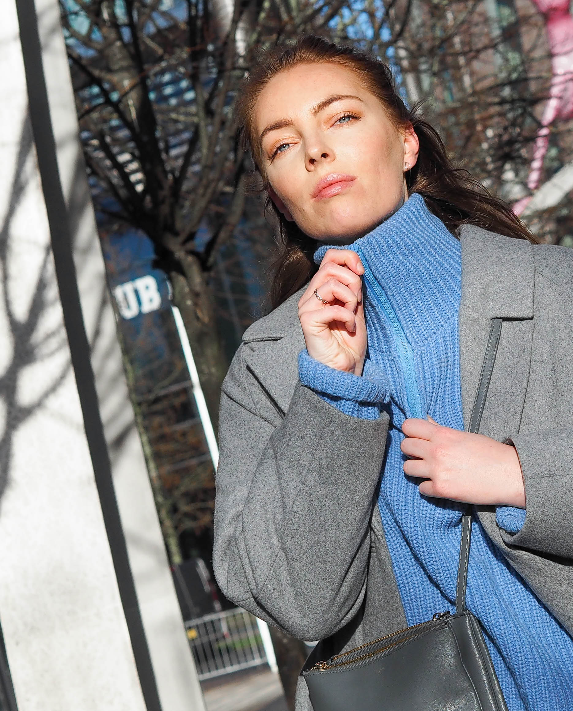 girl with blue eyes wearing blue knit and grey wool coat