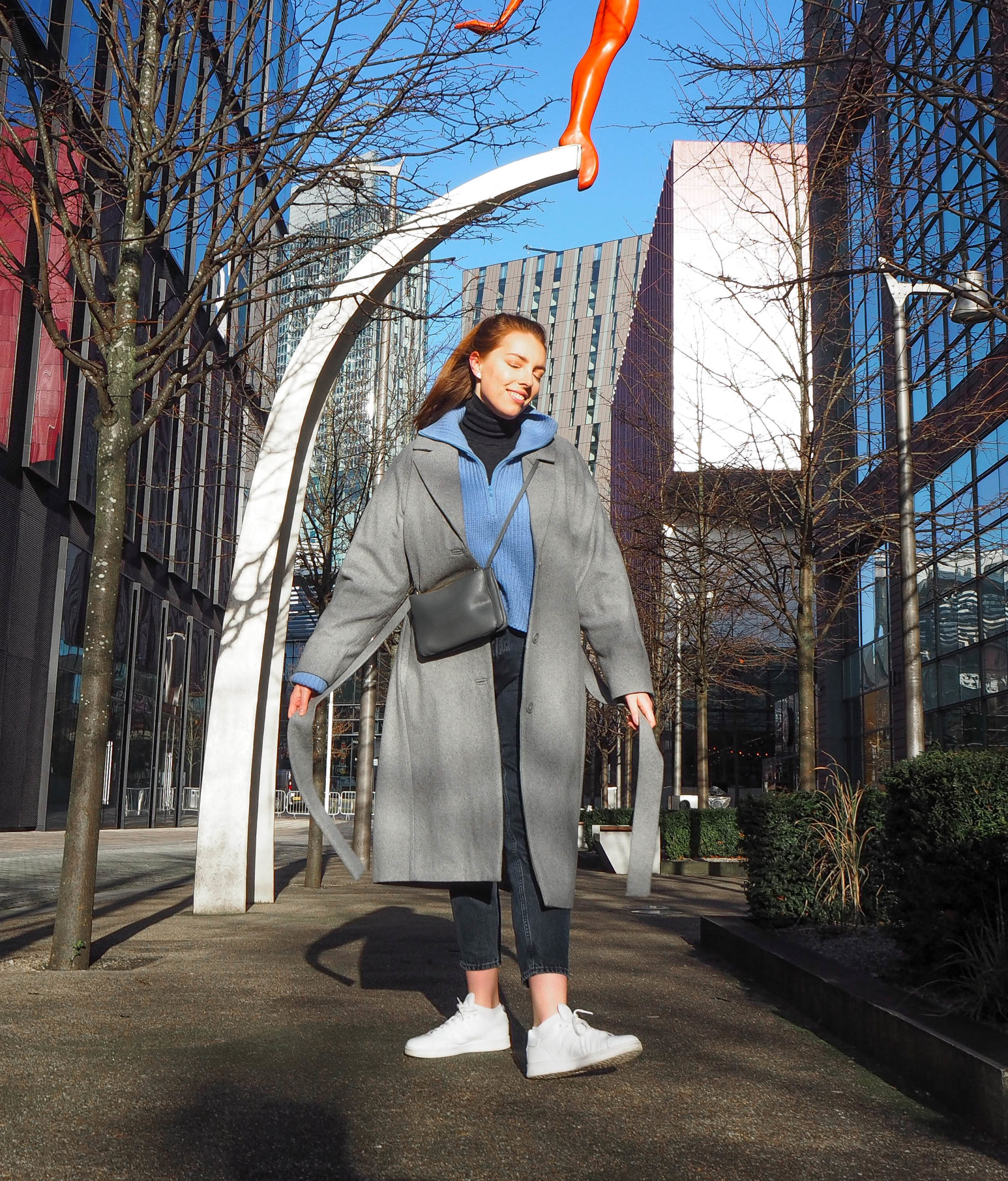 street style photograph girl wearing long grey coat with blue knitwear and white trainers