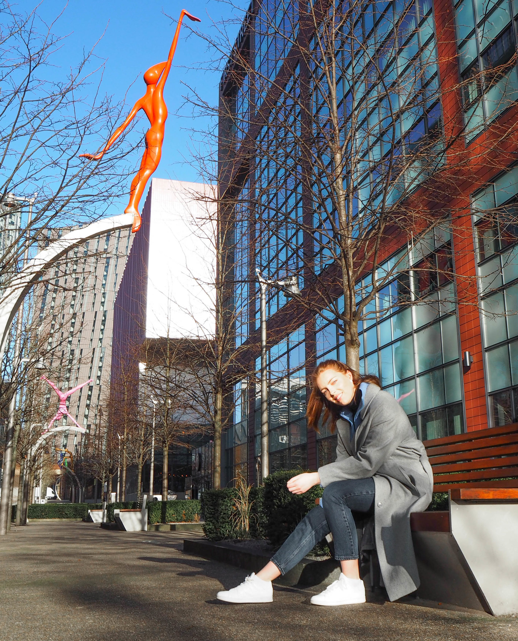 girl sitting on bench wearing long grey coat and white trainers