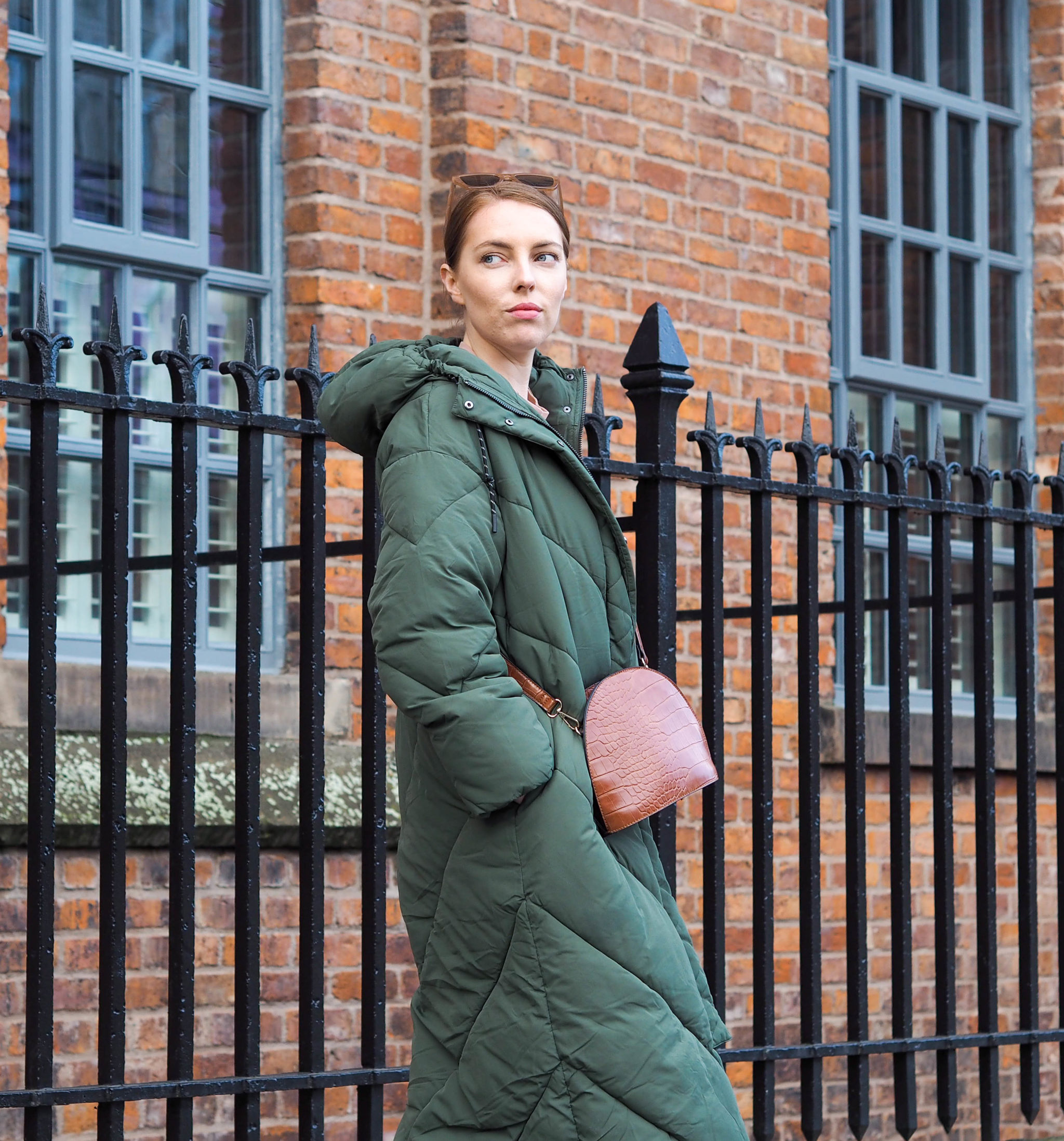 girl wears long green puffer coat