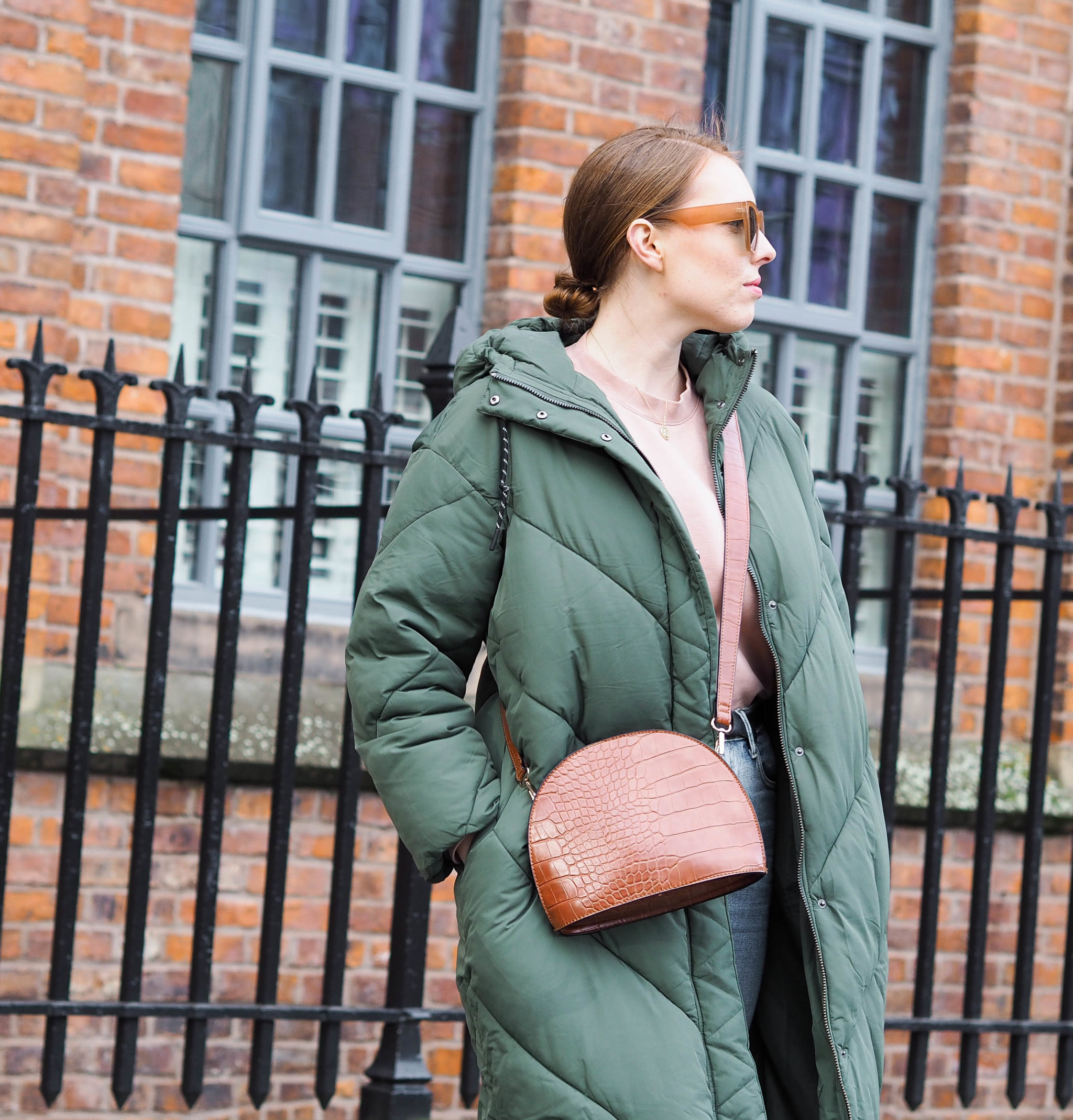 girl wears oversized sunglasses and green padded coat