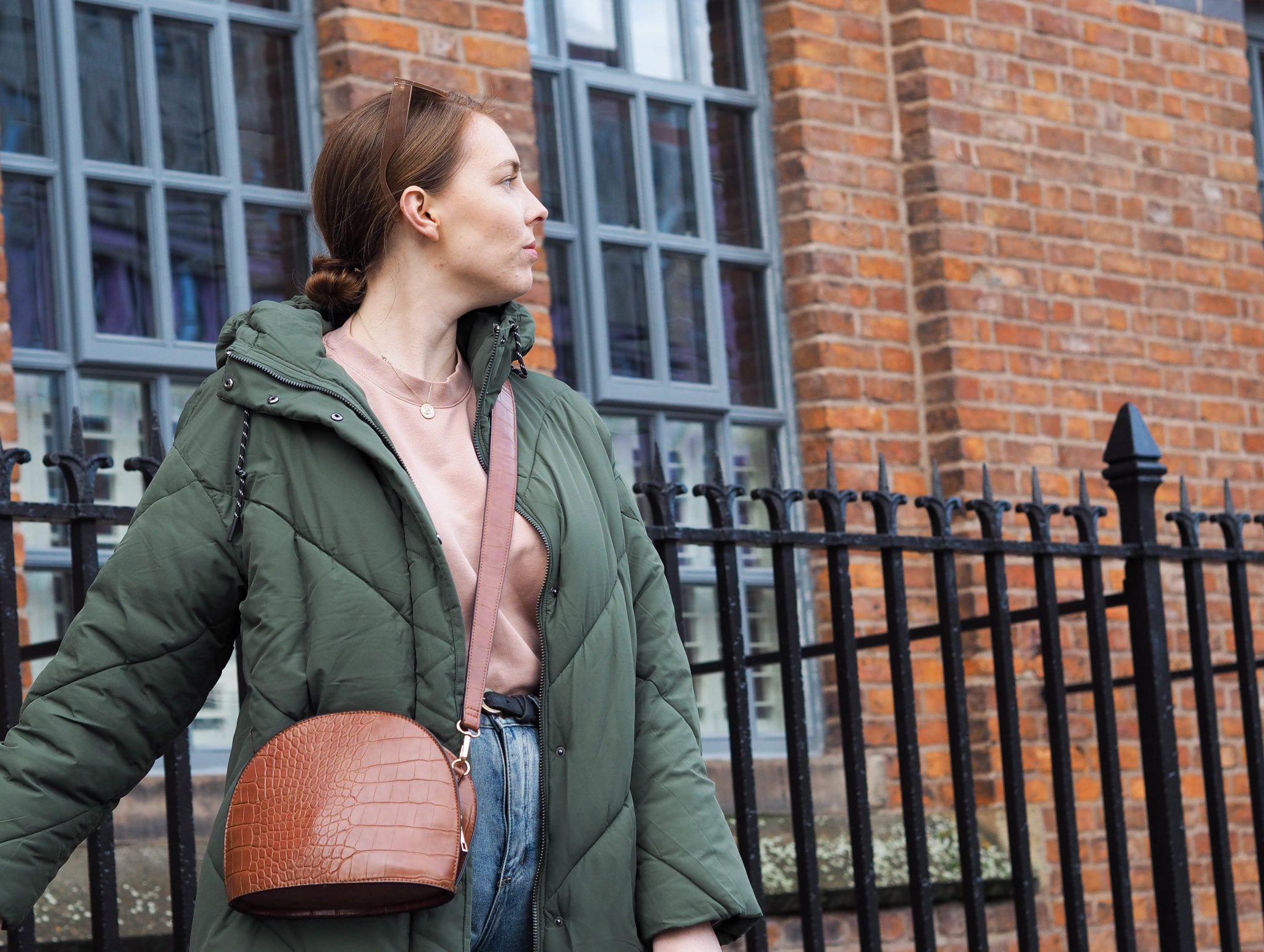 girl wears green puffer coat and brown croc print cross body bag