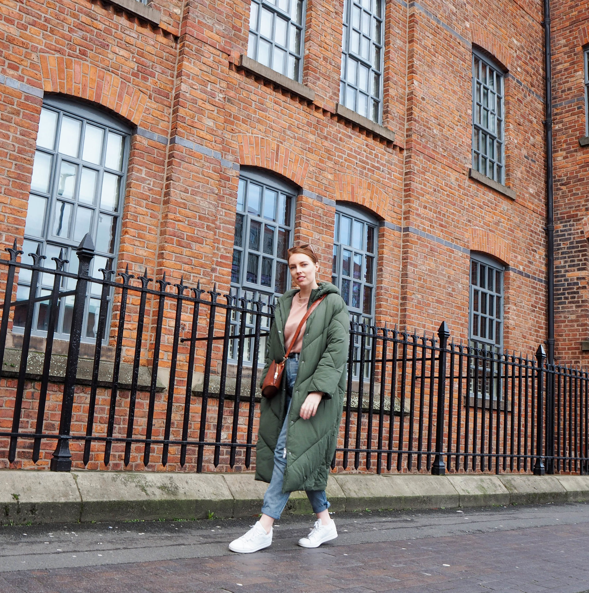 girl wears long khaki puffer coat and white trainers