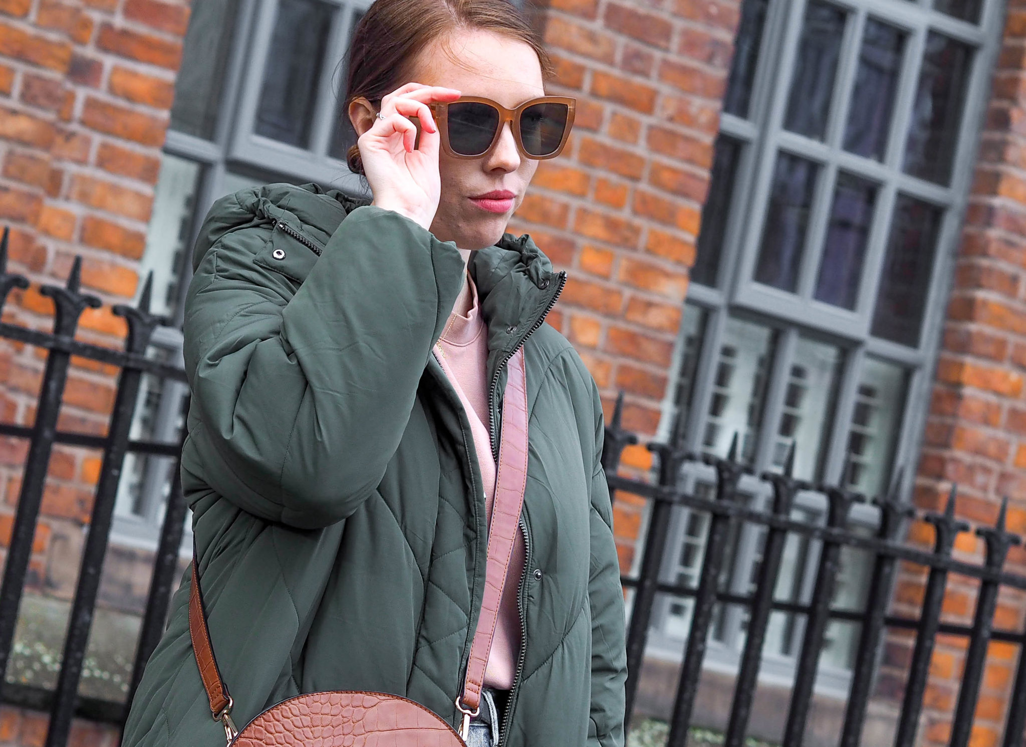 girl wears oversized sunglasses and green puffer jacket