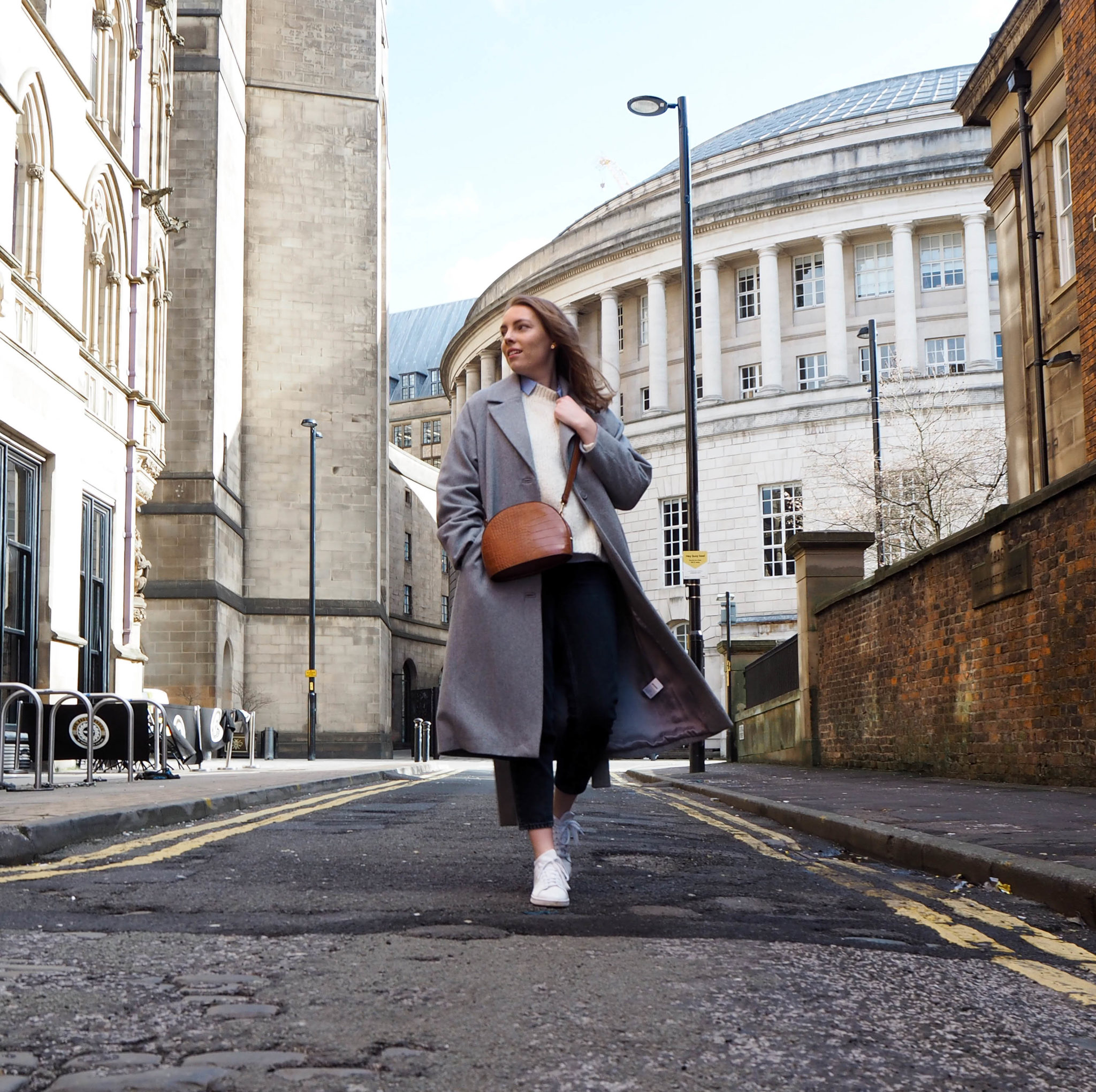 young woman wearing long grey coat and white Adidas trainers in Manchester street style shot