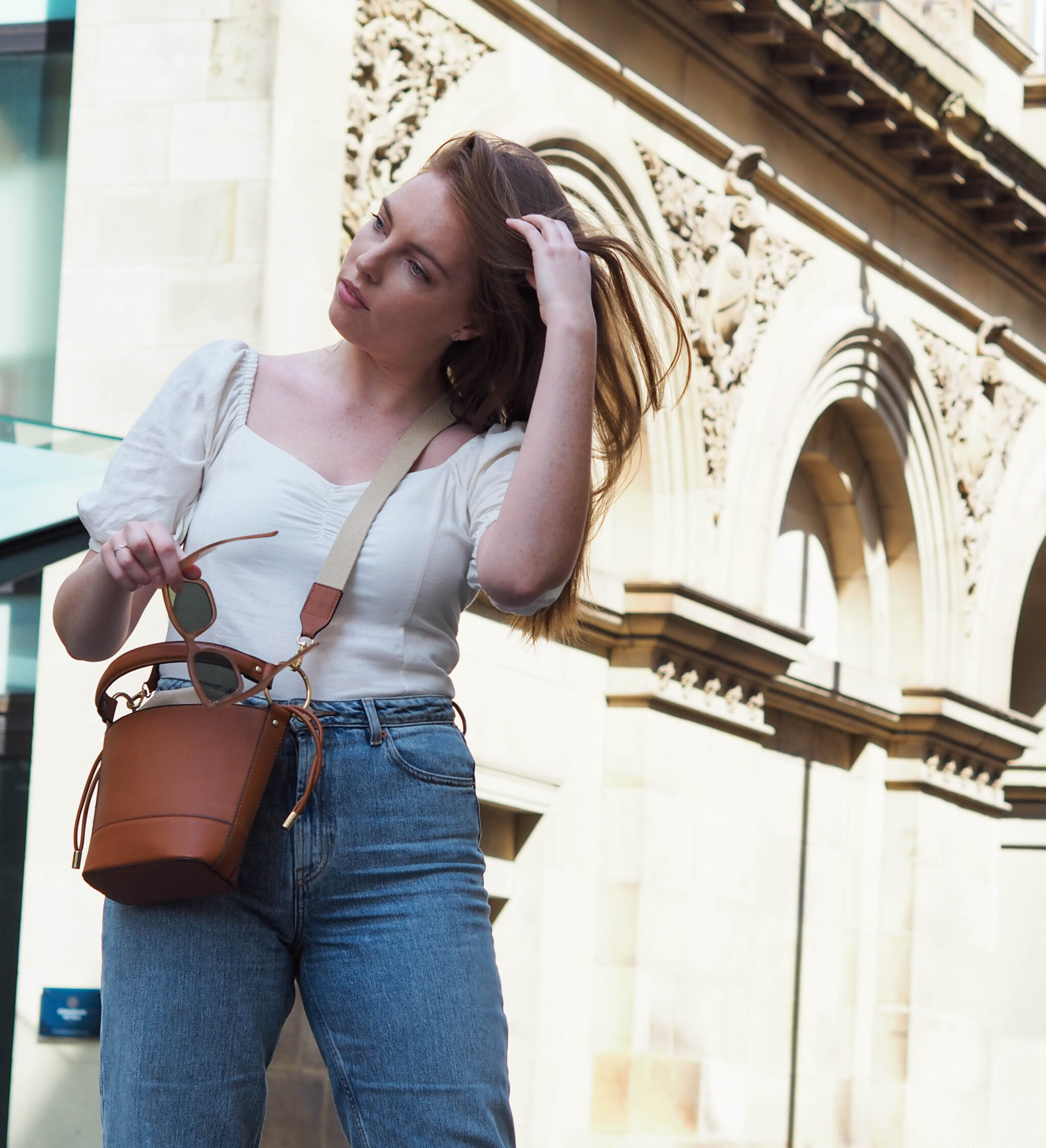 street style shot of girl wearing recycled jeans and white linen top
