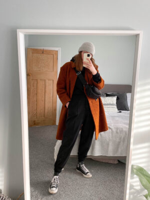 black tracksuit and wool orange coat and chuck Taylor converse lockdown style